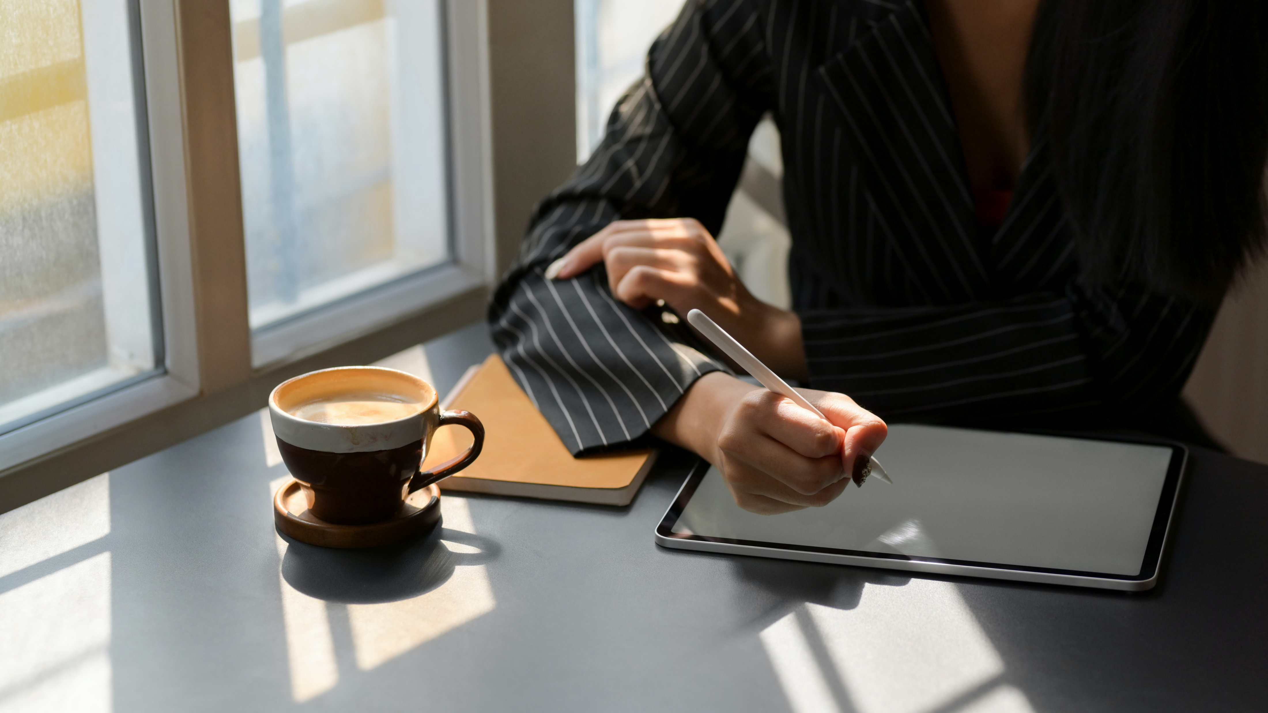 Person, slightly off-screen, using tablet on a desk with a notebook and coffee
